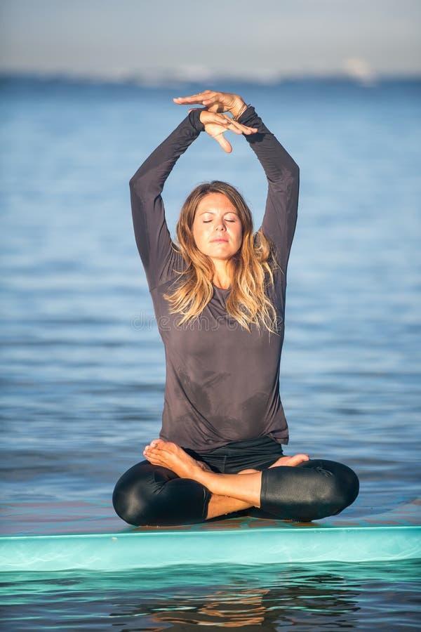 Mujer bonita en la meditación después de su yoga del SORBO en el agua fotografía de archivo libre de regalías