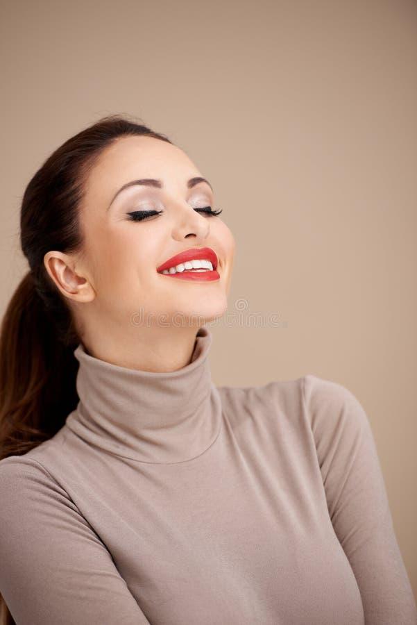 Mujer bonita en la moda cerrada del cuello que sueña despierto fotos de archivo