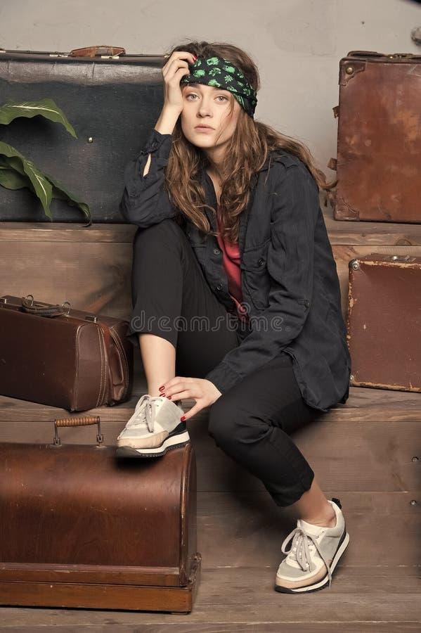 Mujer bonita en pañuelo cerca de la maleta y del bolso del viaje imagen de archivo