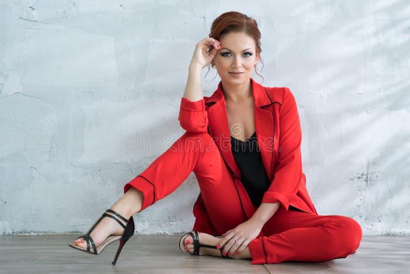 Mujer bonita en pantsuit rojo de moda en estudio fotos de archivo libres de regalías