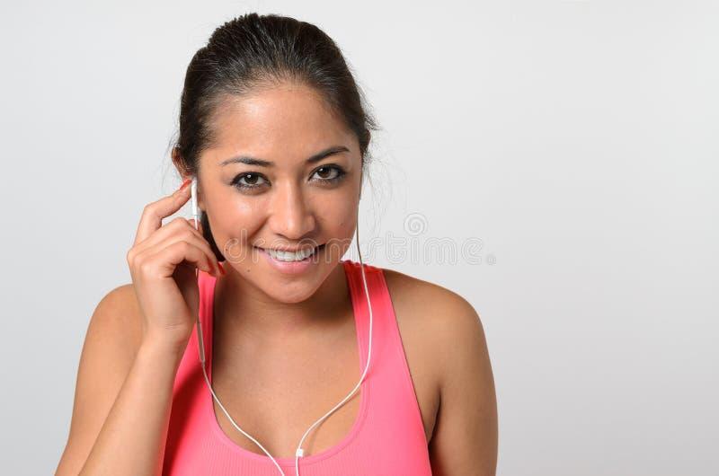 Mujer bonita en top rosado con auriculares de botón en blanco fotografía de archivo