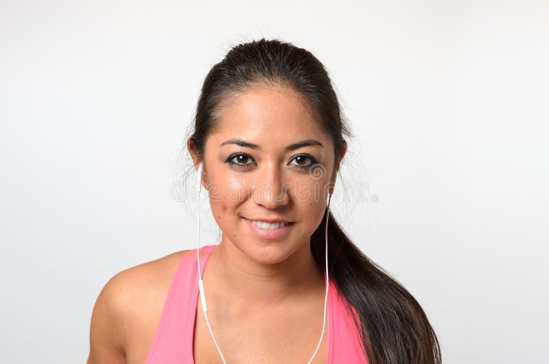 Mujer bonita en top rosado con auriculares de botón en blanco foto de archivo libre de regalías