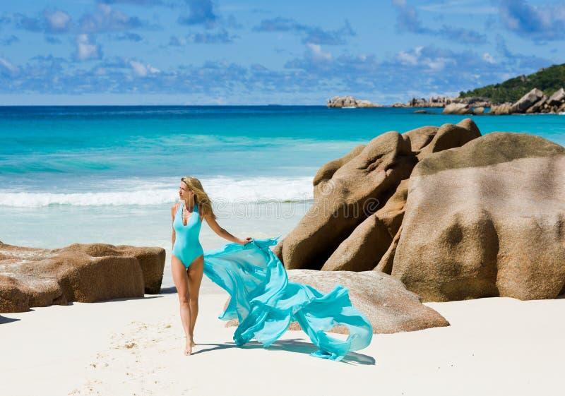 Mujer bonita en traje de baño de los azules turquesa, en la playa ideal, Seychelles fotografía de archivo
