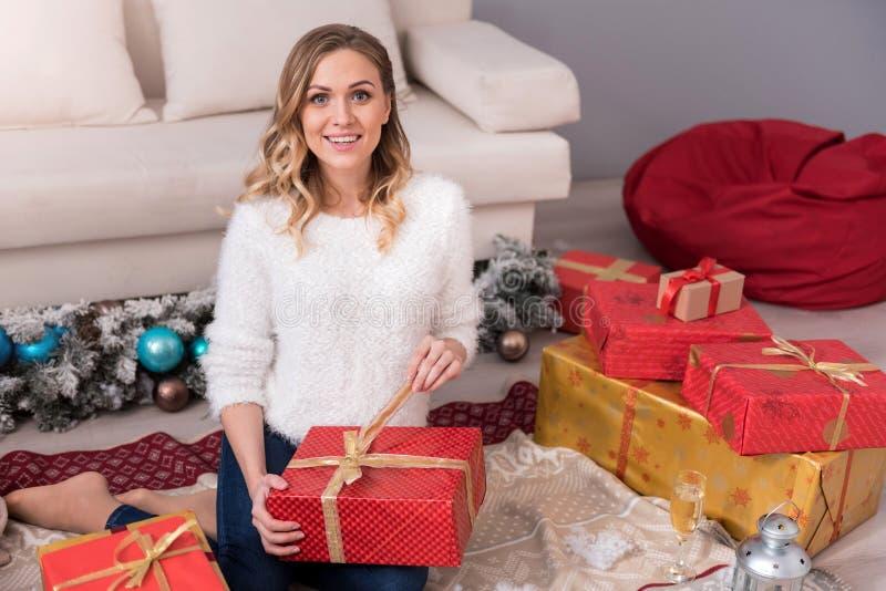Mujer bonita encantadora que desempaqueta su regalo fotografía de archivo libre de regalías