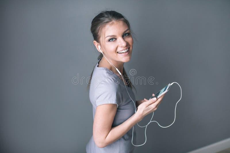 Mujer bonita feliz en auriculares que escucha la música y que sostiene el teléfono móvil imagenes de archivo
