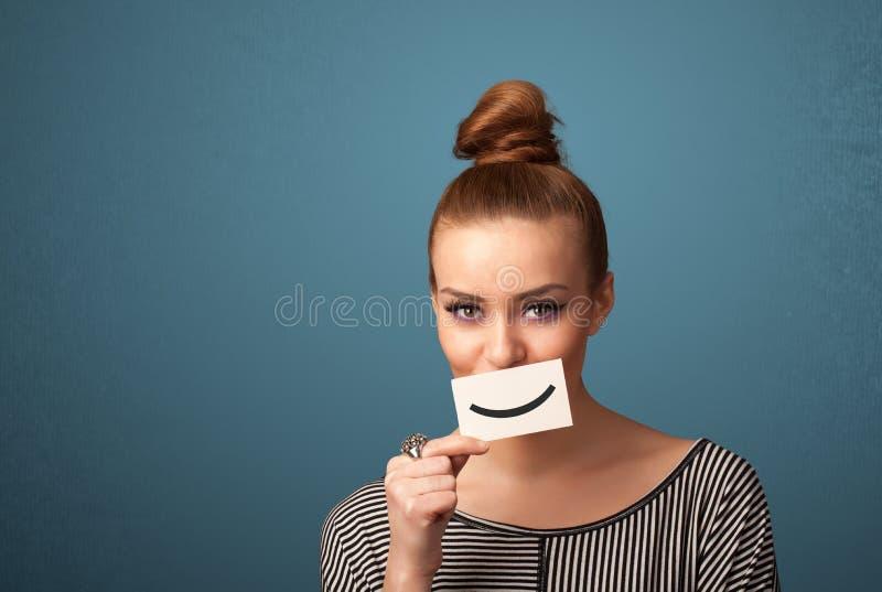 Mujer bonita feliz que sostiene la tarjeta con smiley divertido fotos de archivo libres de regalías