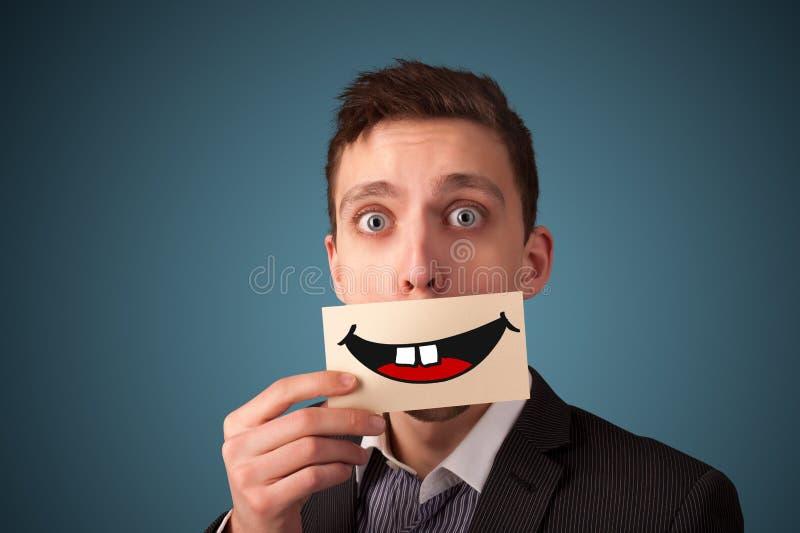 Mujer bonita feliz que sostiene la tarjeta con smiley divertido imagen de archivo