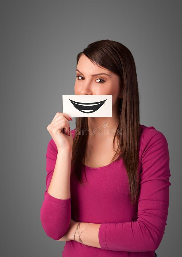 Mujer bonita feliz que sostiene la tarjeta con smiley divertido imagen de archivo libre de regalías