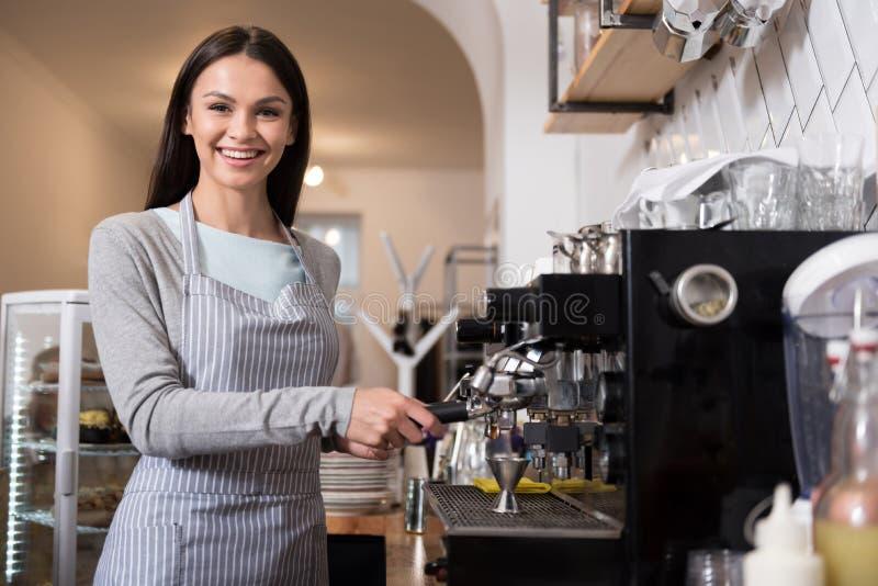 Mujer bonita feliz que usa la máquina del café fotos de archivo