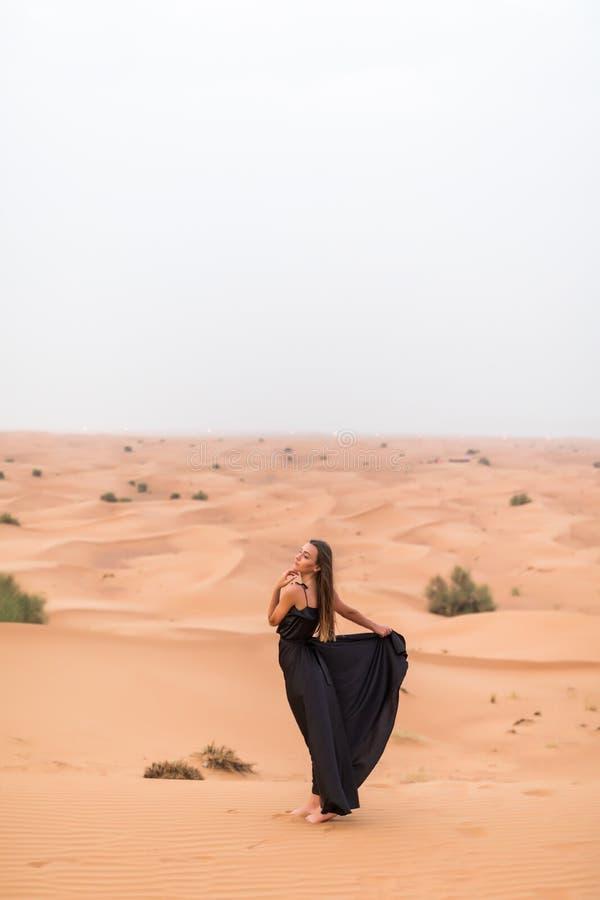 Mujer bonita hermosa en vestido negro en una duna de arena del desierto fotografía de archivo