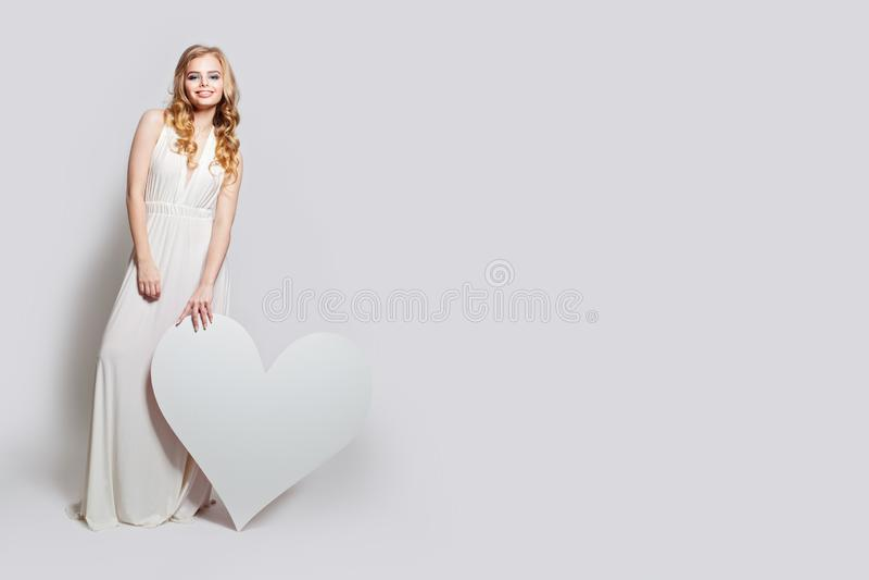 Mujer bonita hermosa que lleva a cabo el fondo blanco del corazón Muchacha del modelo de moda en vestido blanco perfecto imagen de archivo libre de regalías
