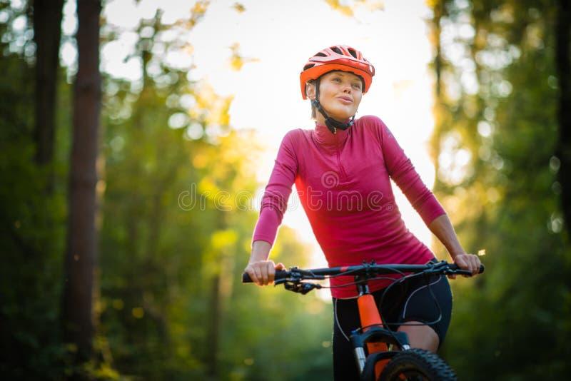 Mujer bonita, joven biking en una bici de montaña imágenes de archivo libres de regalías