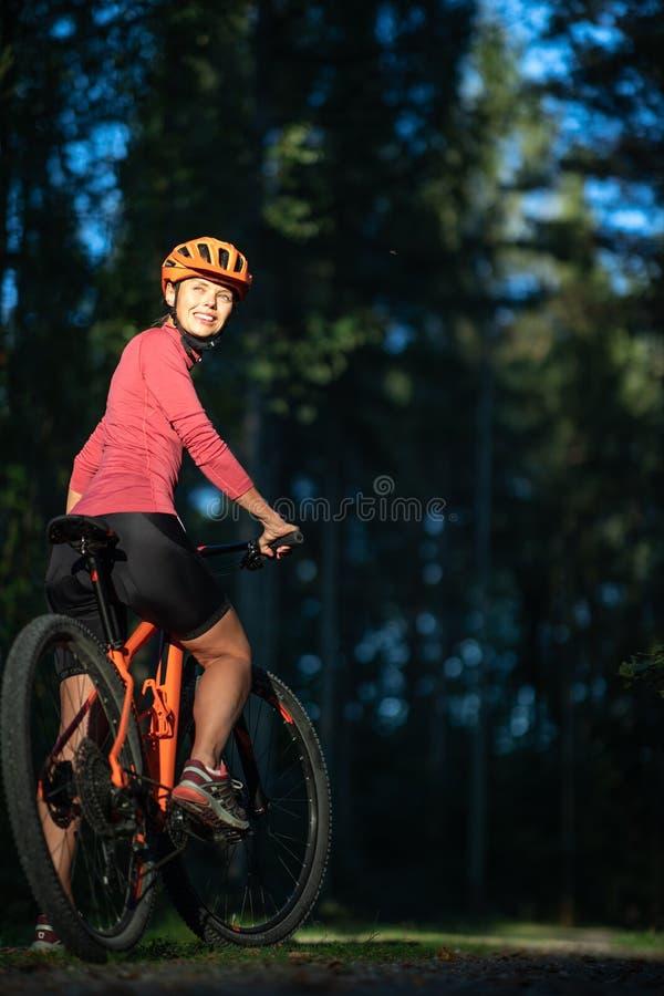 Mujer bonita, joven biking en una bici de montaña foto de archivo libre de regalías