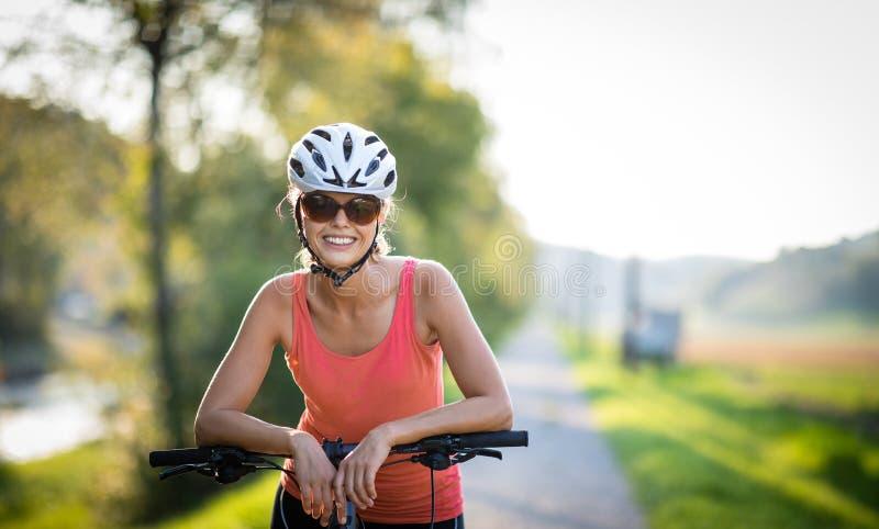 Mujer bonita, joven biking en una bici de montaña fotografía de archivo libre de regalías
