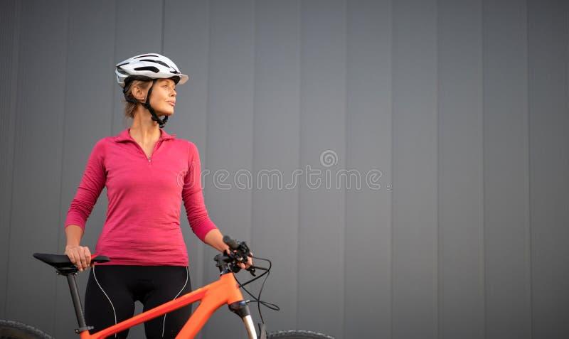 Mujer bonita, joven biking en una bici de montaña imagen de archivo