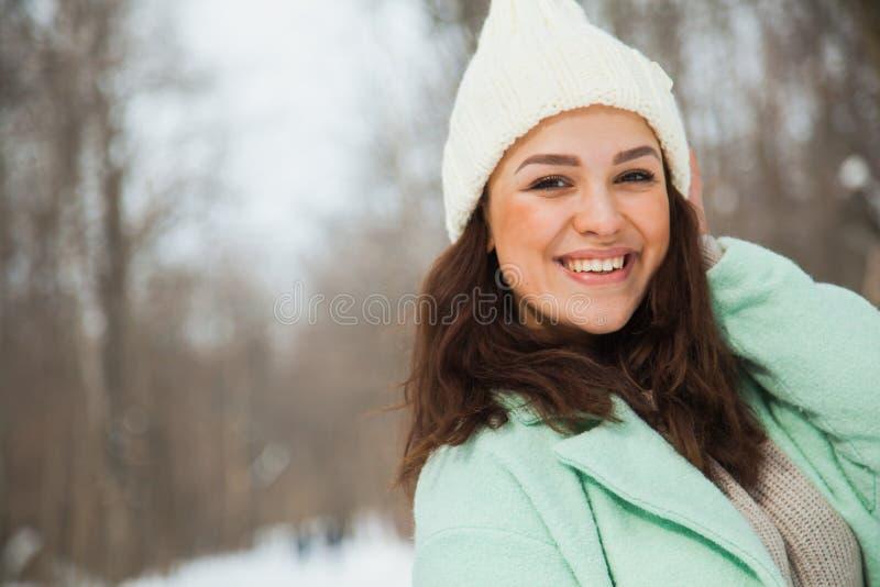 Mujer bonita joven con el sombrero tejido a mano blanco feliz de la sonrisa n fotos de archivo libres de regalías
