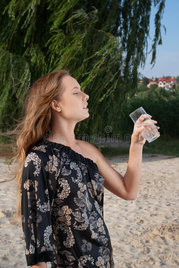 Mujer bonita joven con el vidrio con agua en la playa imagen de archivo libre de regalías