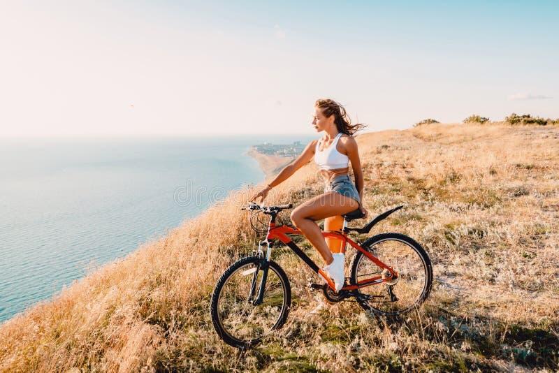 Mujer bonita joven con la bicicleta de la montaña en la camisa blanca, pantalones cortos y zapatillas de deporte blancas fotografía de archivo