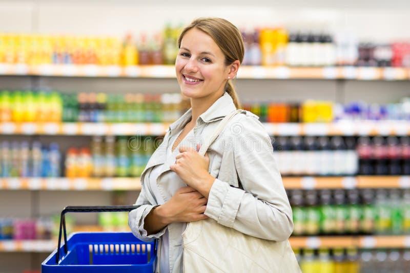Mujer bonita, joven con los ultramarinos de compra de una cesta de compras imagenes de archivo