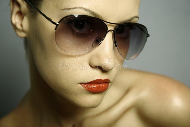 Mujer bonita joven con los vidrios imagen de archivo