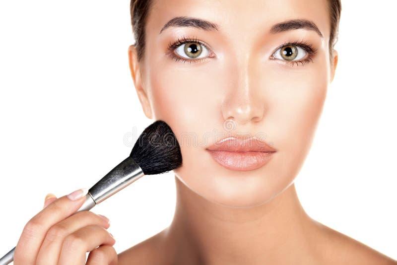 Mujer bonita joven con un cepillo del maquillaje, aislado en blanco imágenes de archivo libres de regalías