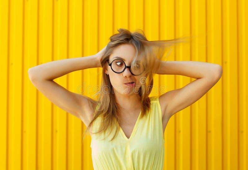 Mujer bonita joven divertida que lleva a cabo las manos en su cabeza y que intenta a fotografía de archivo