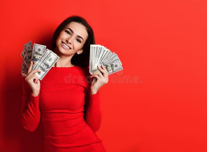 Mujer bonita joven en el vestido rojo que oculta detrás del manojo de billetes de banco del dinero imagenes de archivo