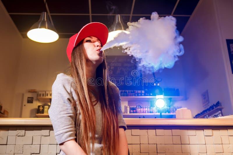 Mujer bonita joven en humo rojo del casquillo un cigarrillo electrónico en la tienda del vape imagen de archivo libre de regalías