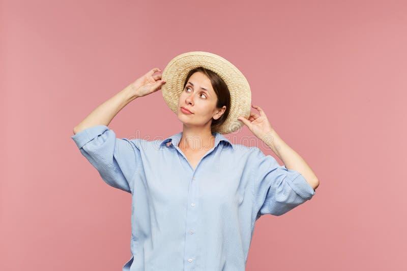 Mujer bonita joven en la camisa azul que intenta el nuevo sombrero imagen de archivo