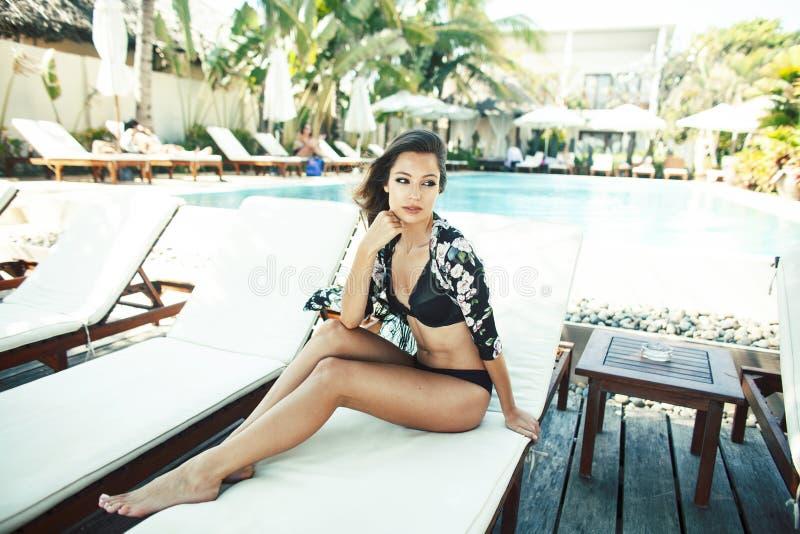 Mujer bonita joven en la piscina que se relaja en la silla, mirada de la moda en la ropa interior en el hotel, concepto de la gen imagenes de archivo