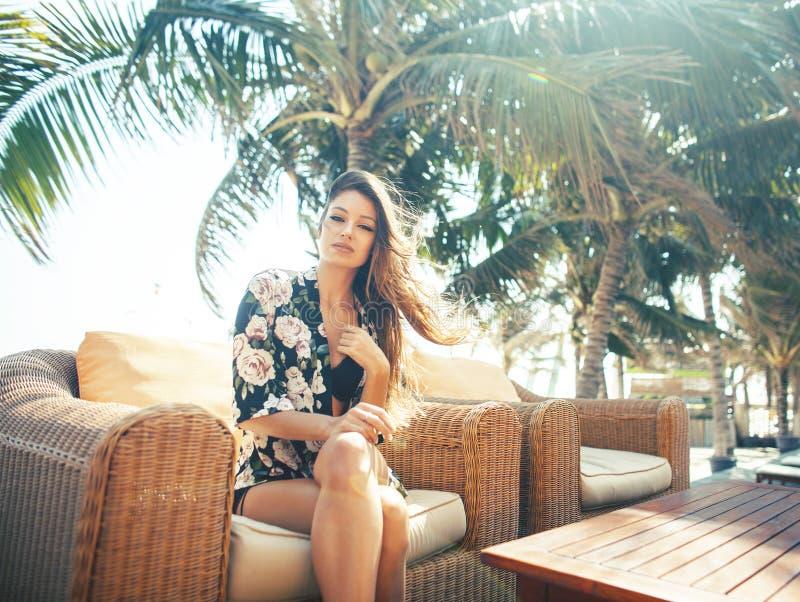 Mujer bonita joven en la piscina que se relaja en la silla, mirada de la moda en la ropa interior en el hotel, concepto de la gen foto de archivo