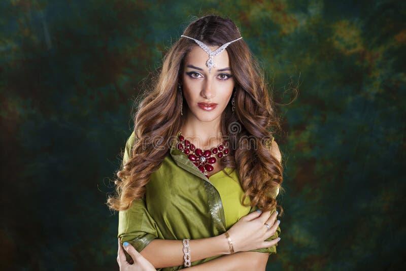 Mujer bonita joven en vestido indio verde imagenes de archivo