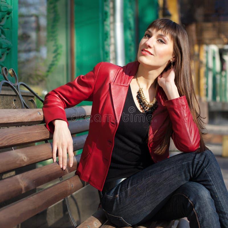 Mujer bonita joven feliz que se sienta en el banco y el d?a de primavera soleado sonriente foto de archivo
