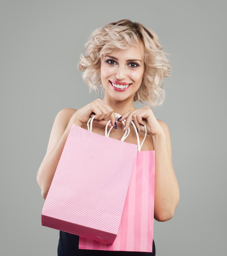 Mujer bonita joven que celebra bolsos y la sonrisa de compras imagen de archivo libre de regalías