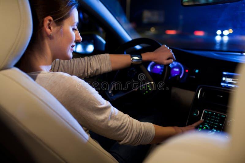 Mujer bonita, joven que conduce su coche moderno fotografía de archivo
