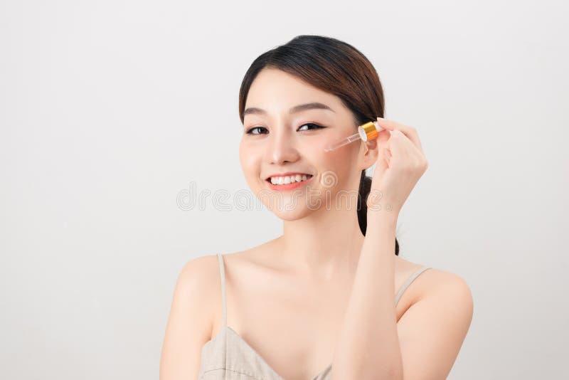 Mujer bonita joven que consigue el tratamiento especial de la piel en el sal?n de belleza Muchacha hermosa que aplica el suero de imagen de archivo