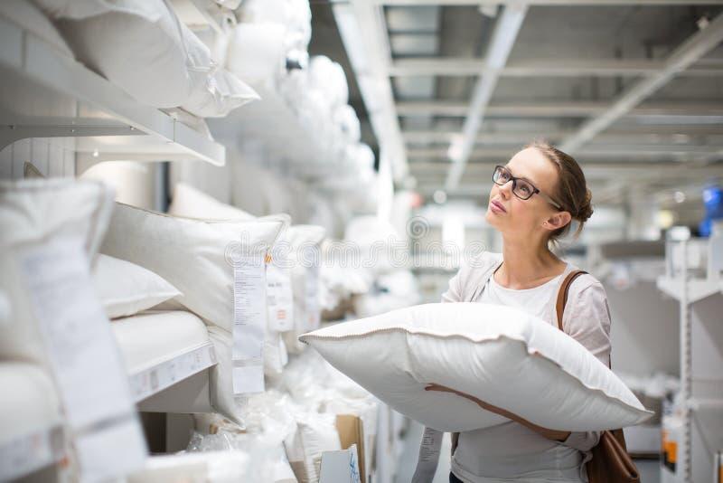 Mujer bonita, joven que elige la almohada derecha imagen de archivo libre de regalías