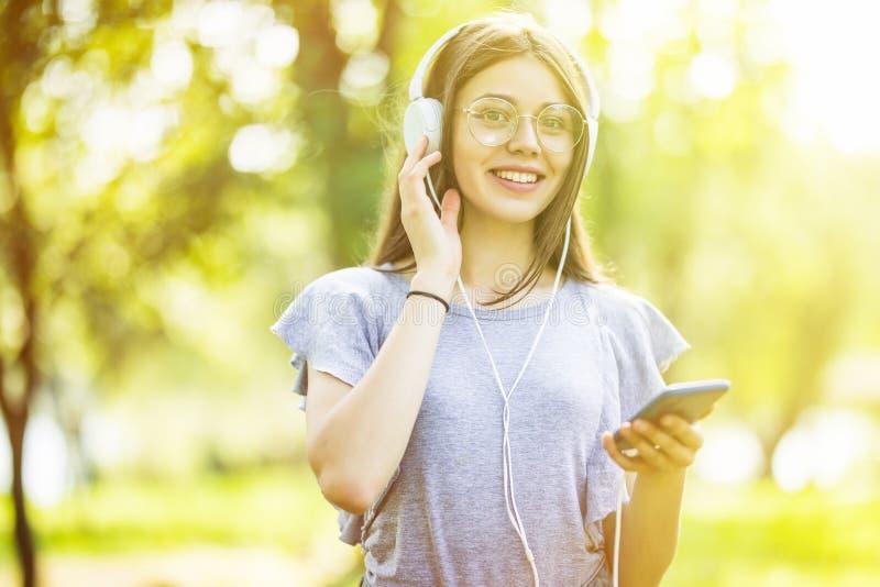 Mujer bonita joven que escucha la música y que camina en el parque fotografía de archivo