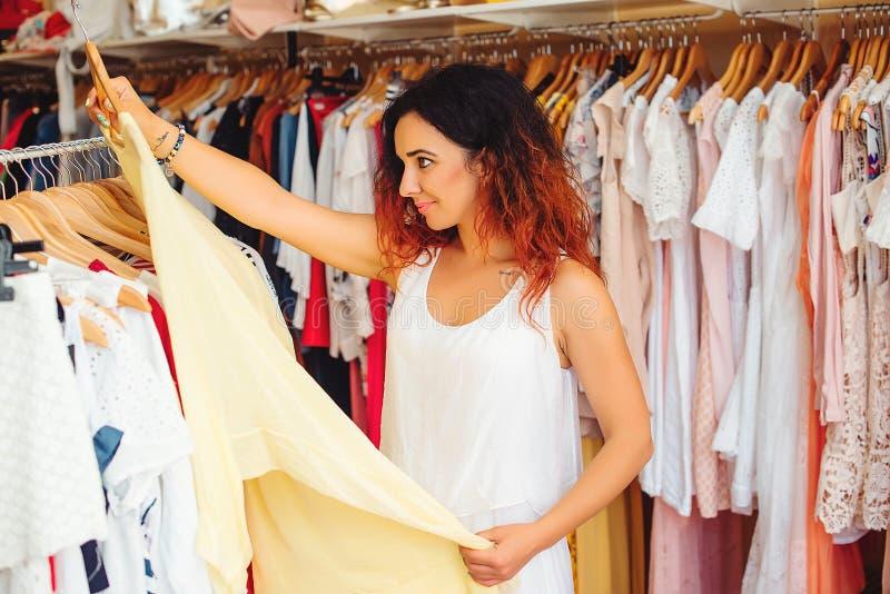 Mujer bonita joven que intenta en el nuevo vestido en tienda de ropa Tiempo de las compras Venta del verano imagen de archivo