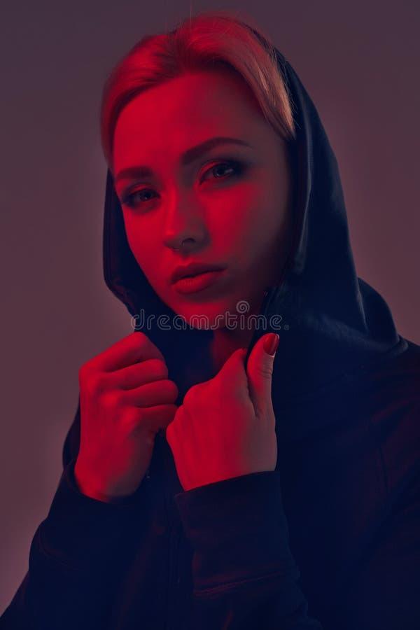 Mujer bonita joven que lleva una capilla negra y pantalones cortos en fondo oscuro Retrato imágenes de archivo libres de regalías