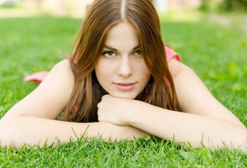 Mujer bonita joven que miente en hierba verde en parque fotos de archivo
