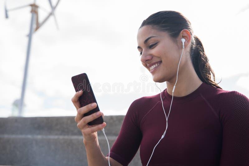 Mujer bonita joven que mira el teléfono imágenes de archivo libres de regalías