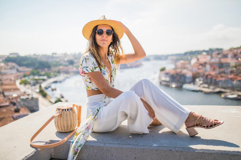 Mujer bonita joven que se sienta en el punto de visión delante del río del Duero y el puente de los Dom luis I en Oporto, Portuga foto de archivo libre de regalías