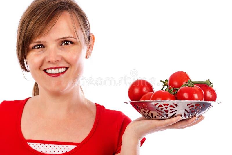 Mujer bonita joven que sostiene un cuenco de tomates maduros imagen de archivo libre de regalías