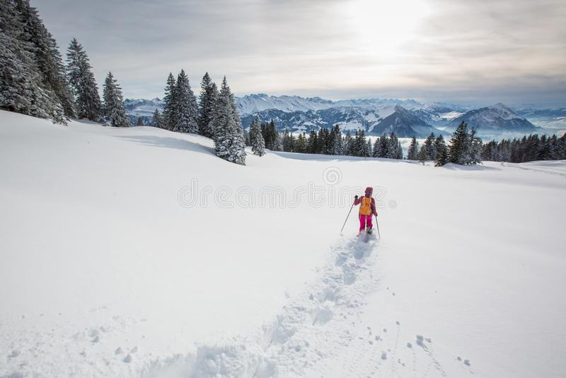 Mujer bonita, joven snowshoeing en altas montañas foto de archivo libre de regalías