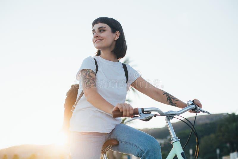 Mujer bonita linda en la bicicleta en puesta del sol fotos de archivo libres de regalías