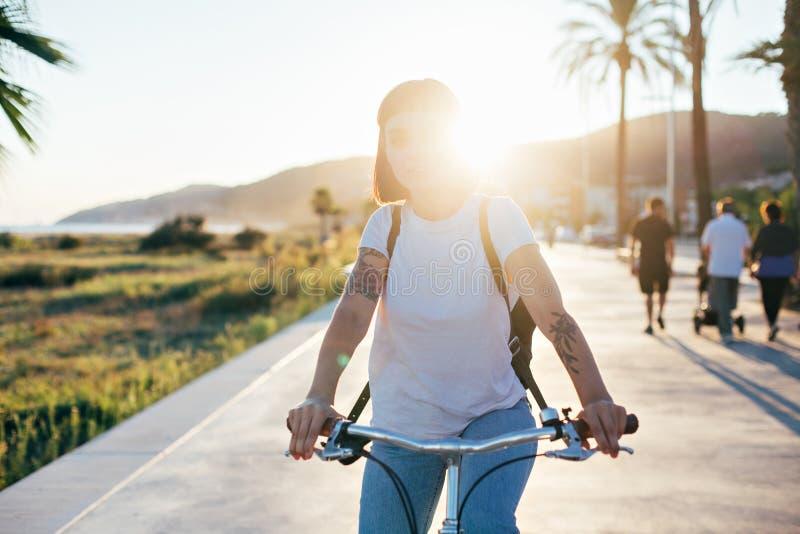 Mujer bonita linda en la bicicleta en puesta del sol imagen de archivo libre de regalías