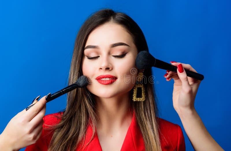 Mujer bonita que aplica el cepillo del maquillaje Tono de piel perfecto Belleza imponente Las fuentes del maquillaje hacen compra foto de archivo libre de regalías