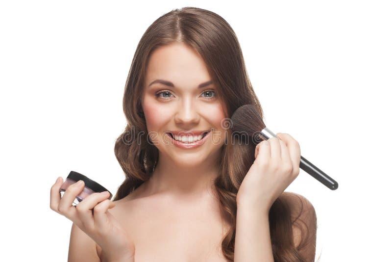 Mujer bonita que aplica maquillaje fotografía de archivo