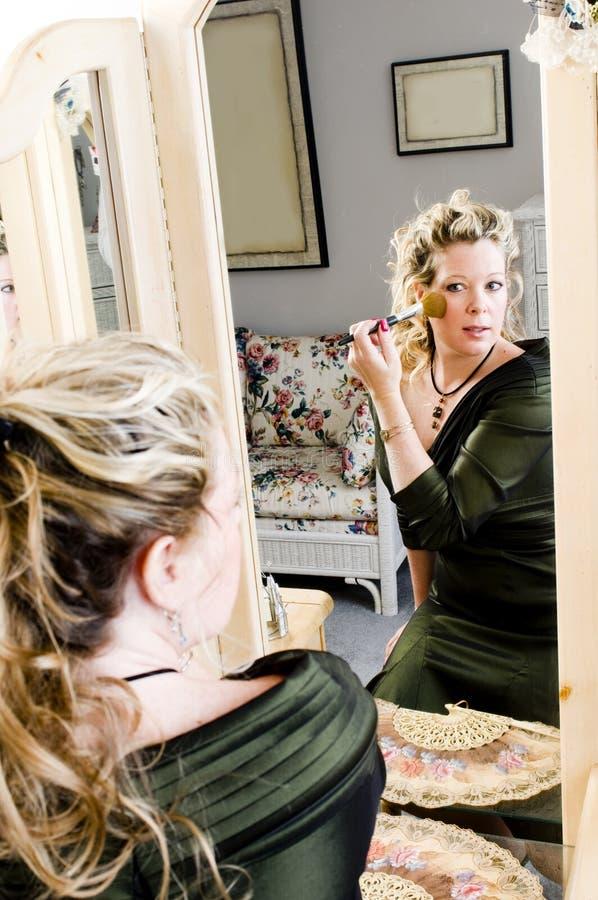 Mujer bonita que aplica maquillaje imagen de archivo